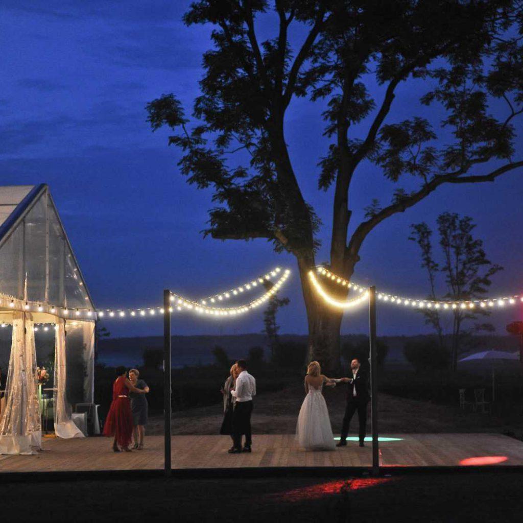 Girlanda żarówkowa tradycyjna oświetla parkiet wesela na otwartym powietrzu