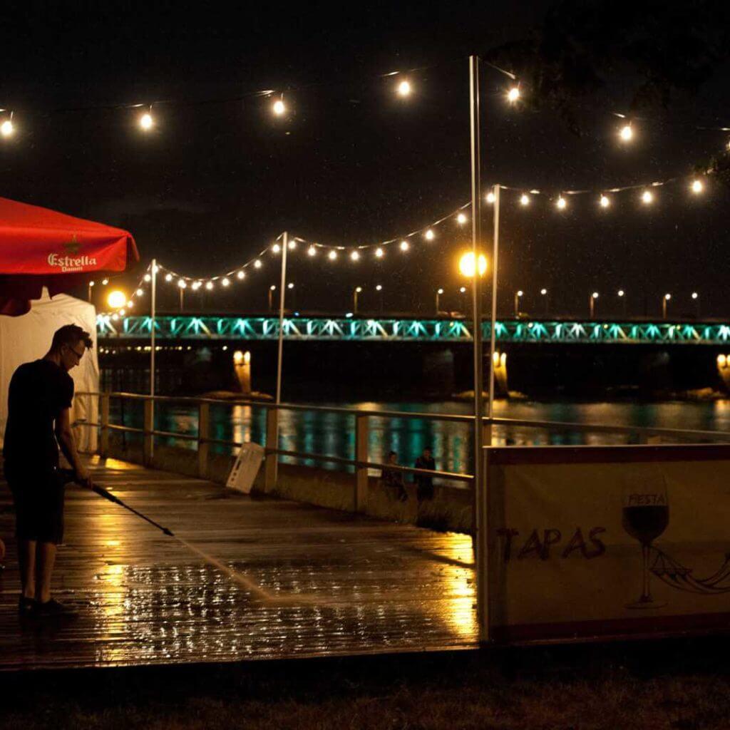 Girlanda nad wisłą w Warszawie. Bar oświetlony nocą.